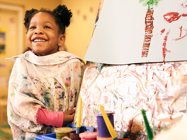 Child using paints at an easel.